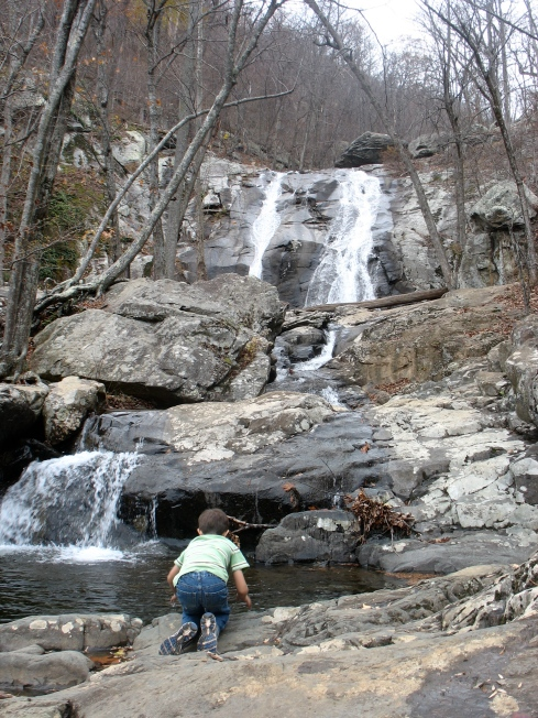 Child playing at base of waterfall.