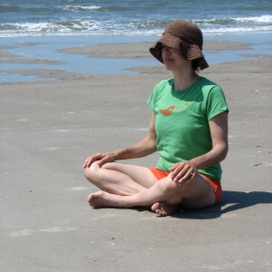 Yoga mama meditating on the beach